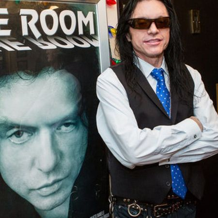 Tommy Wiseau with a poster for The Room.